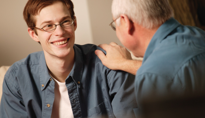 young man receiving praise from older adult male