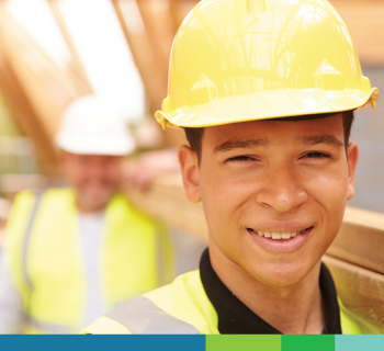 Young man working hard on a construction site and smiling
